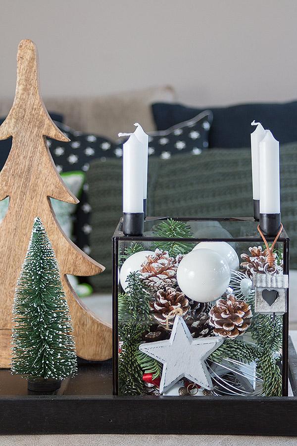 Glaskasten weihnachtlich dekoriert mit frischem Grün und Zapfen