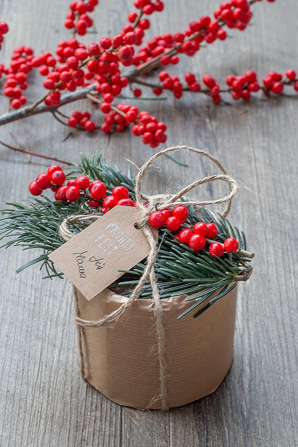 Weihnachtsgeschenk mit Tanne und Ilex dekorieren