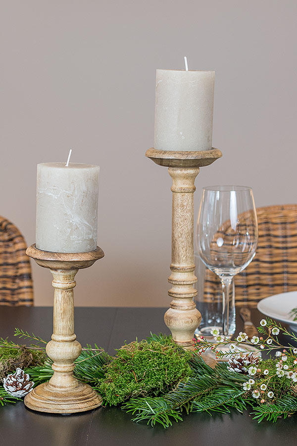 weihnachtlich dekorierter Tisch mit naturfarbenen Kerzenständern