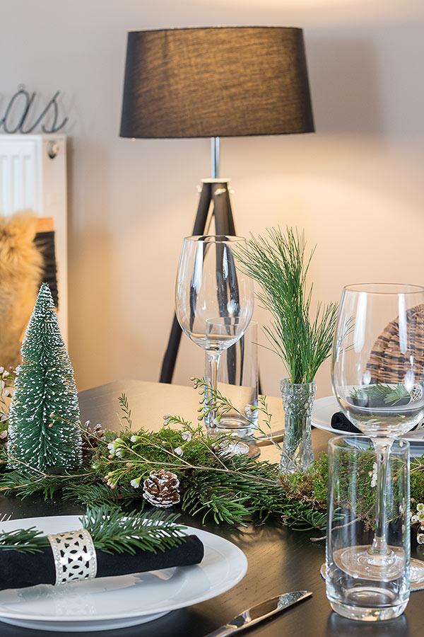weihnachtliche Tischdeko mit Tanne, Moos und Wachsblumen