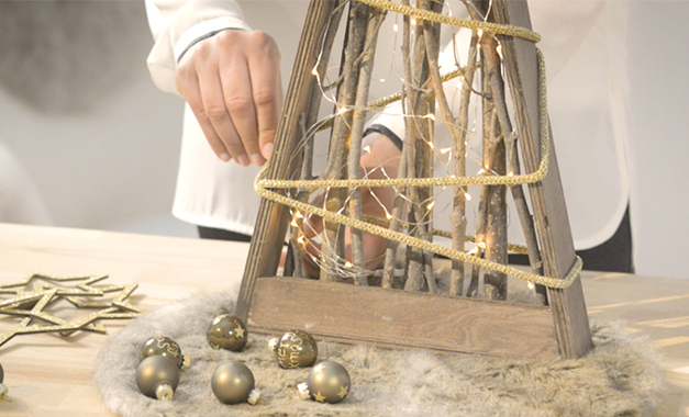 Das goldene Band wird um das Dekoobjekt gewickelt und geknotet. Es dient anschließend als Befestigung für die Sterne.