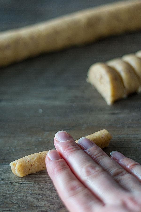 Kleine Teigstücke für Vanillekipferl mit den Händen zu kleinen Rollen formen