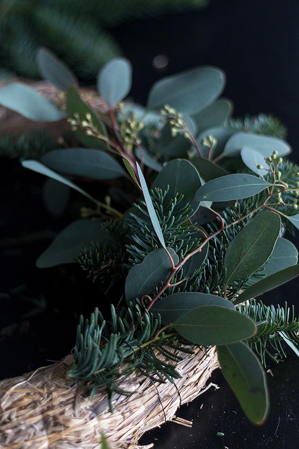Nacheinander die Eukalyptus Nobilis Bündel am Strohkranz befestigen