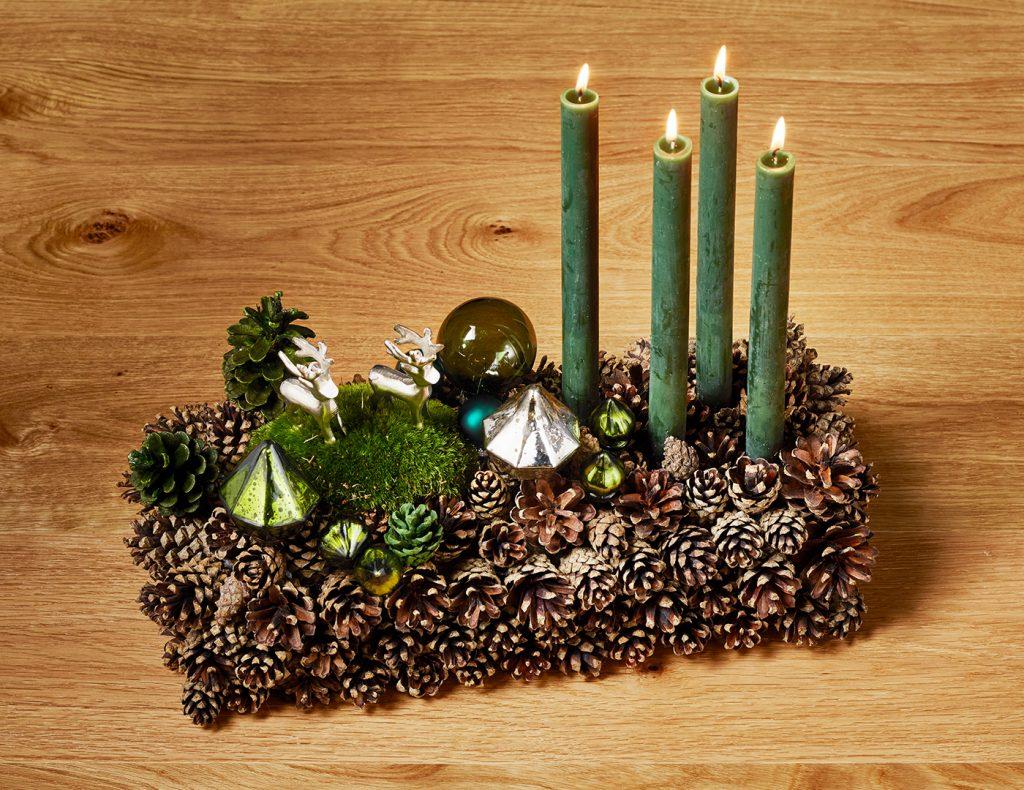 Kleine Weihnachtskugeln und Ornamente bilden funkelnde Highlights zwischen den Naturmaterialien.