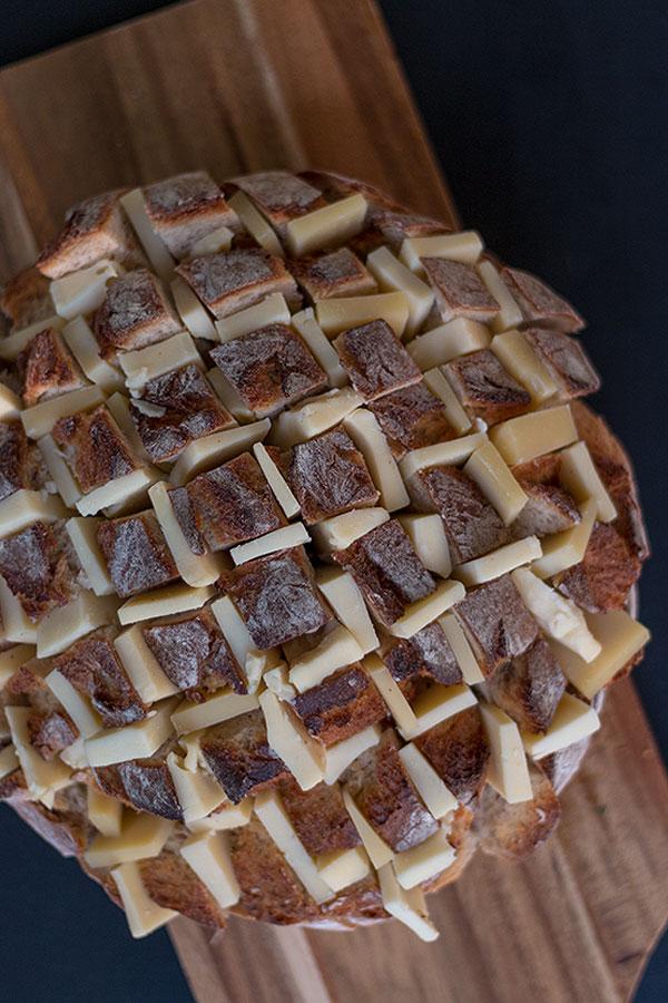 Brot gitterartig einschneiden und mit Käse bestücken