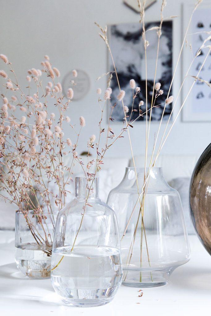 schlichte-filigrane-glasvasen-mit-graesern-als-wohnzimmerdeko