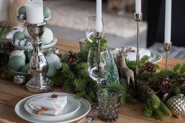 Weihnachtstischdeko mit Tanne, Moos, Zapfen und Weihnachtskugeln