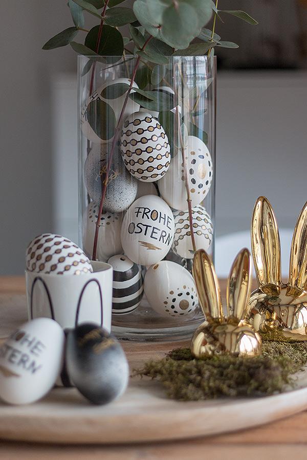 Ostereier gestalten in Schwarz, Weiß, Gold und dekoriert in einer Vase mit Zweigen
