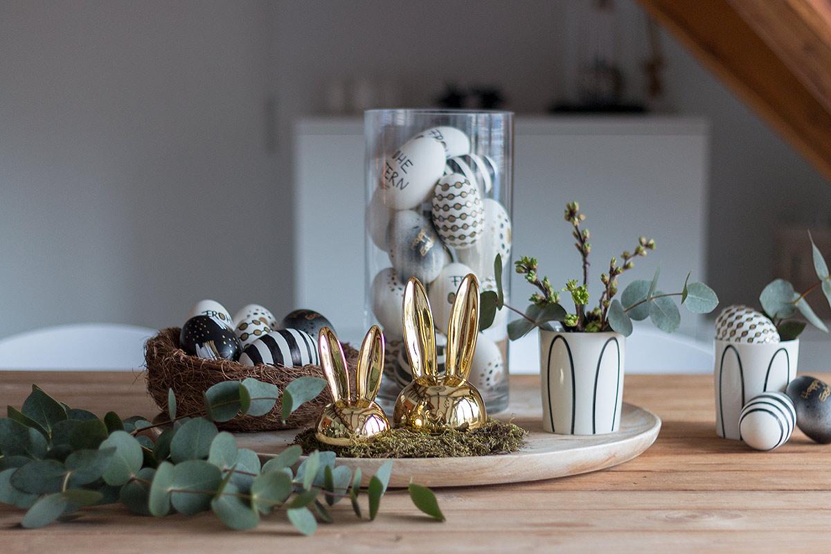 Ostertischdeko mit Schwarz, Weiß, Gold gestalteten Ostereiern und Eukalyptus