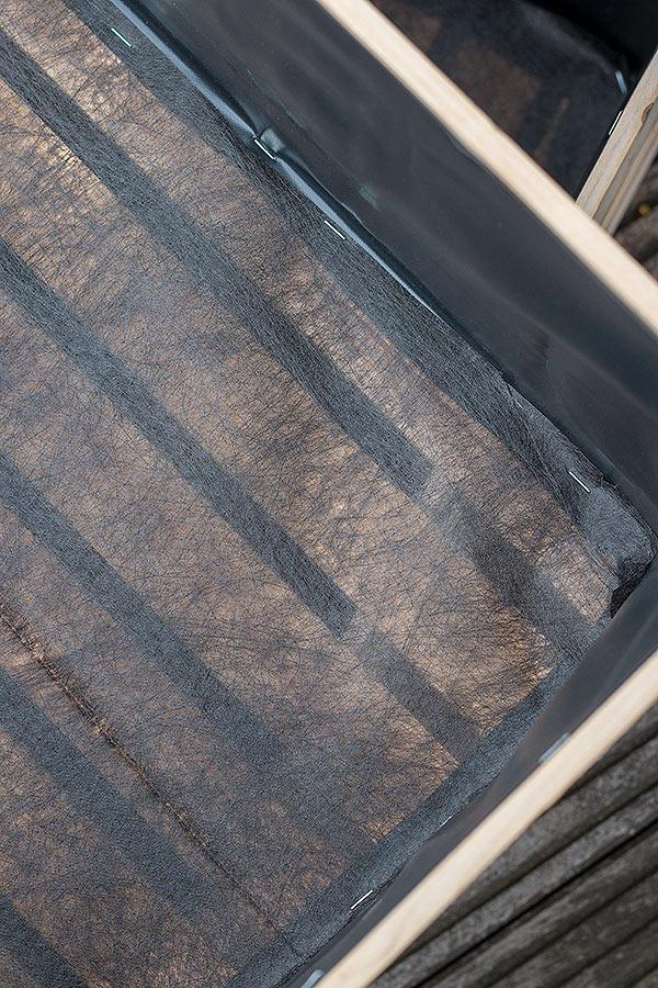 Holzkiste für den Kräutergarten mit durchlässigem Gartenvlies am Boden festtackern