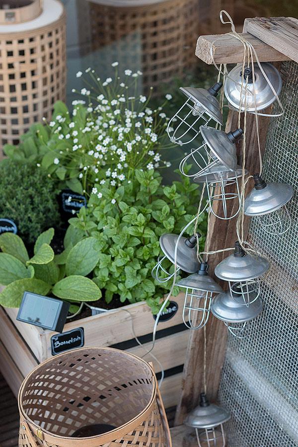 Solarlichterketten lassen den Kräutergarten in Holzkisten auch nach Sonnenuntergang strahlen