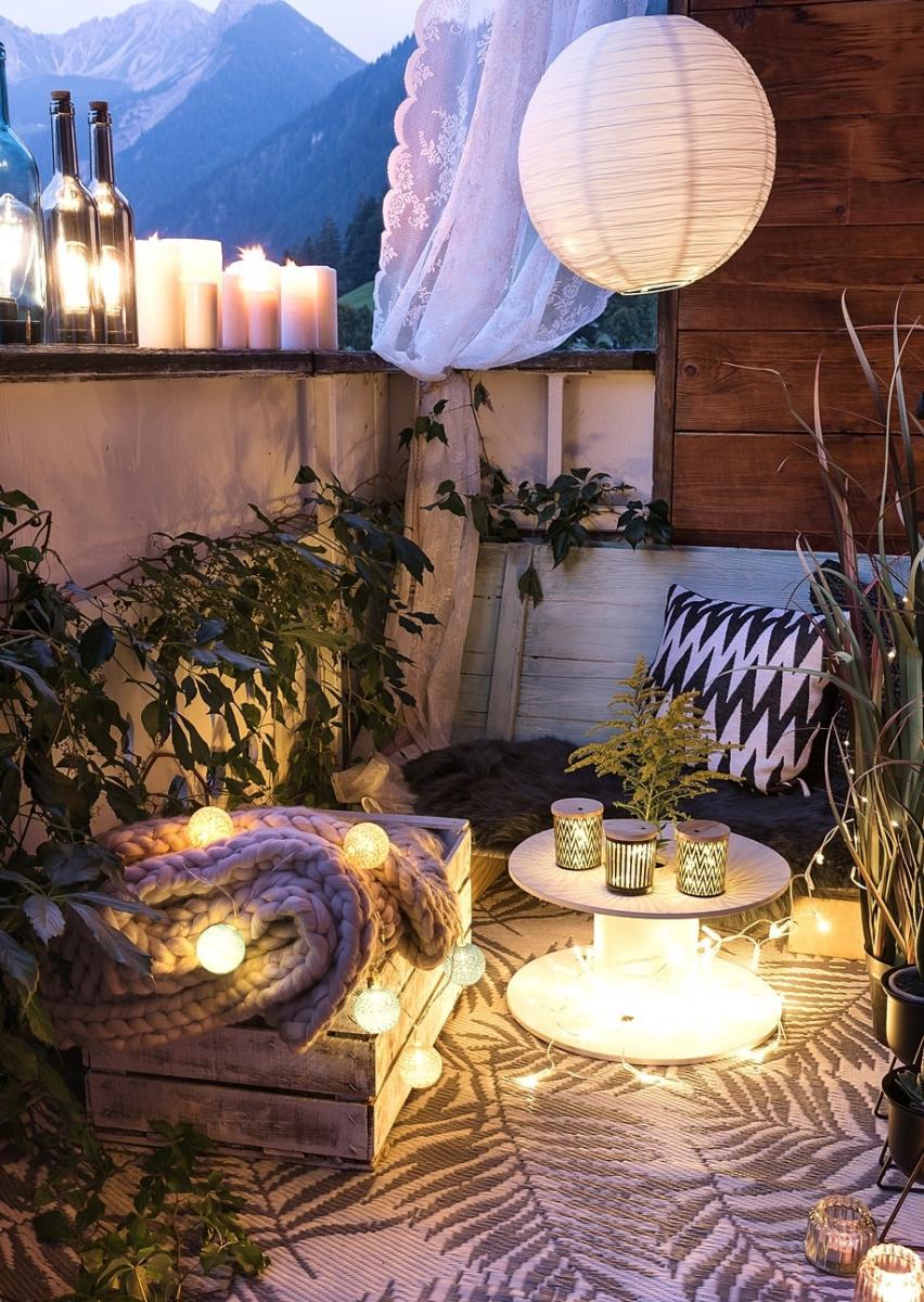 Stimmungsvolle Balkondeko mit Lichterketten und Windlichtern.