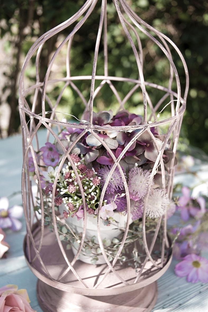 Dekokäfig mit Lichterkette und Kunstblumen schmücken