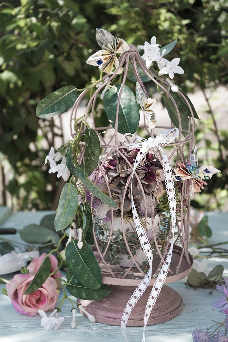 DIY-Geldgeschenk: Dekokäfig geschmückt mit Blumen und gefalteten Geldscheinen