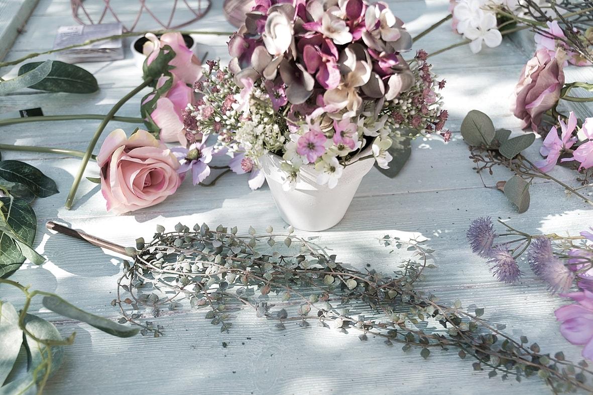 Blumengesteck aus Kunstblumen und Blättergirlande