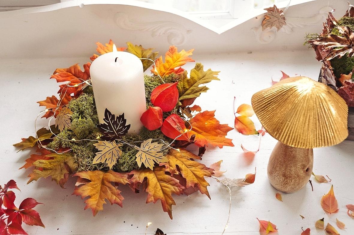Schale mit Kerze und buntem Herbstlaub.