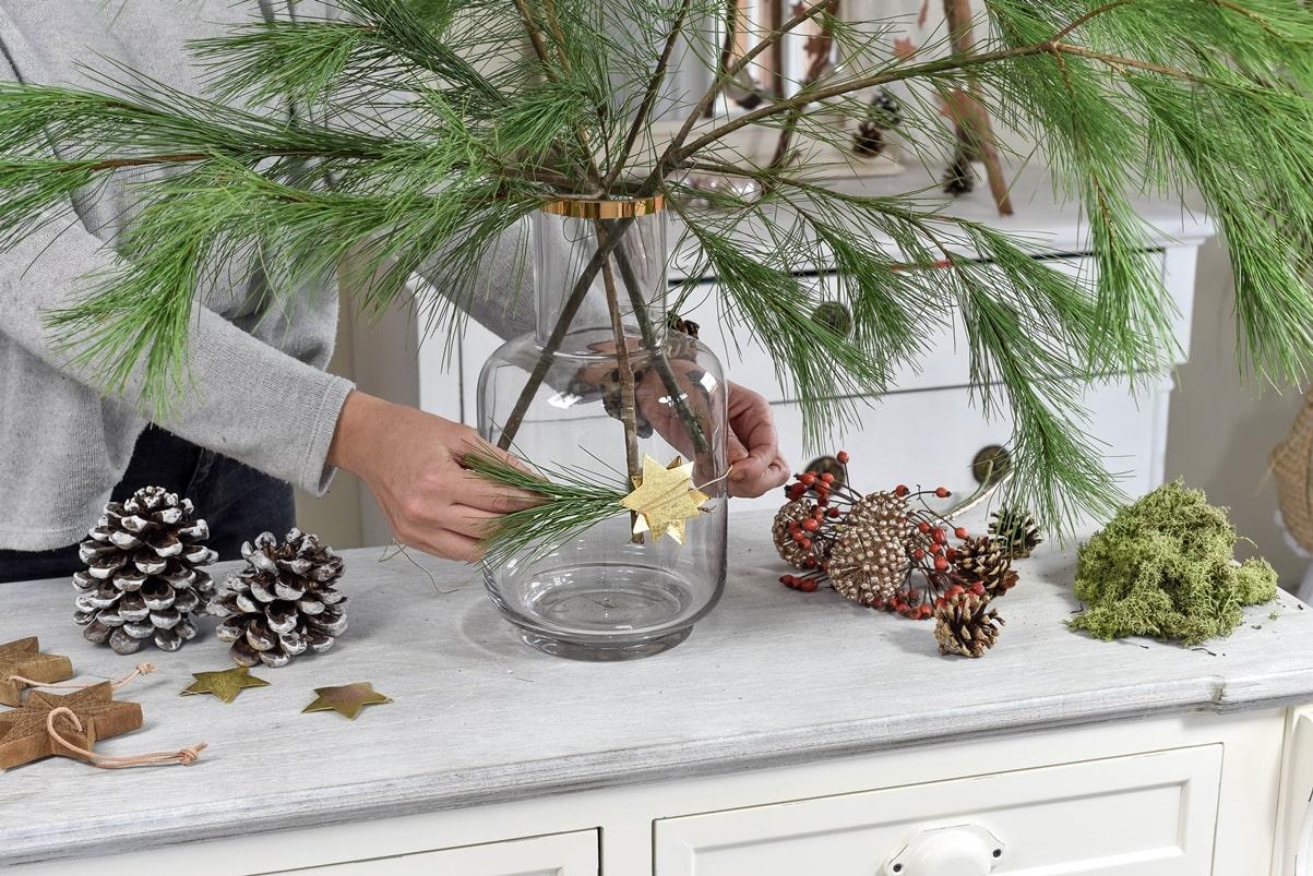 Vase mit Zweig und Stern weihnachtlich schmücken.