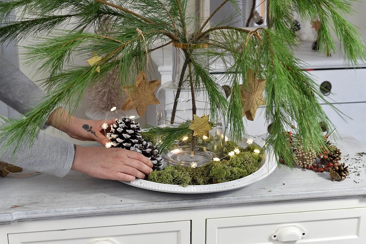 Dekoteller mit Pinienzapfen dekorieren.