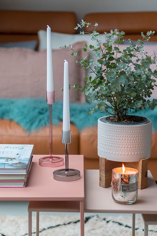 Pastellfarbene Beistelltische dekoriert mit Kerzen, Eukalyptus und Coffee Table Books