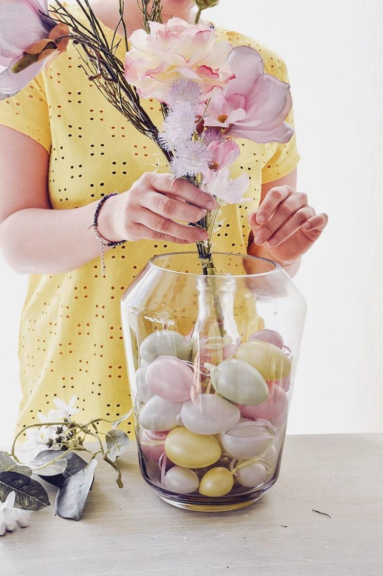 Ostereier und Blumen in die Vase geben