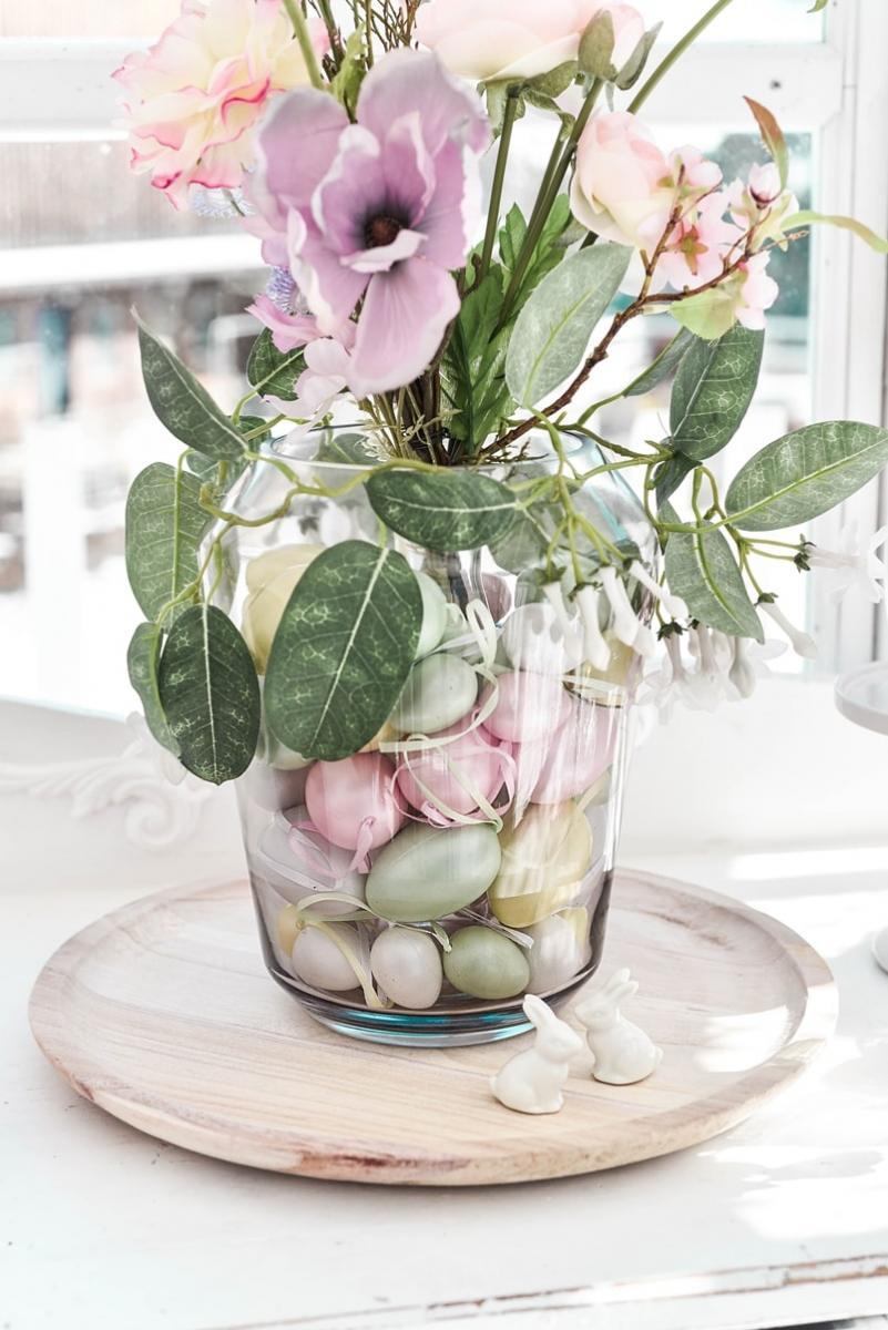 Ostereier und Kunstblumen in der Vase arrangieren