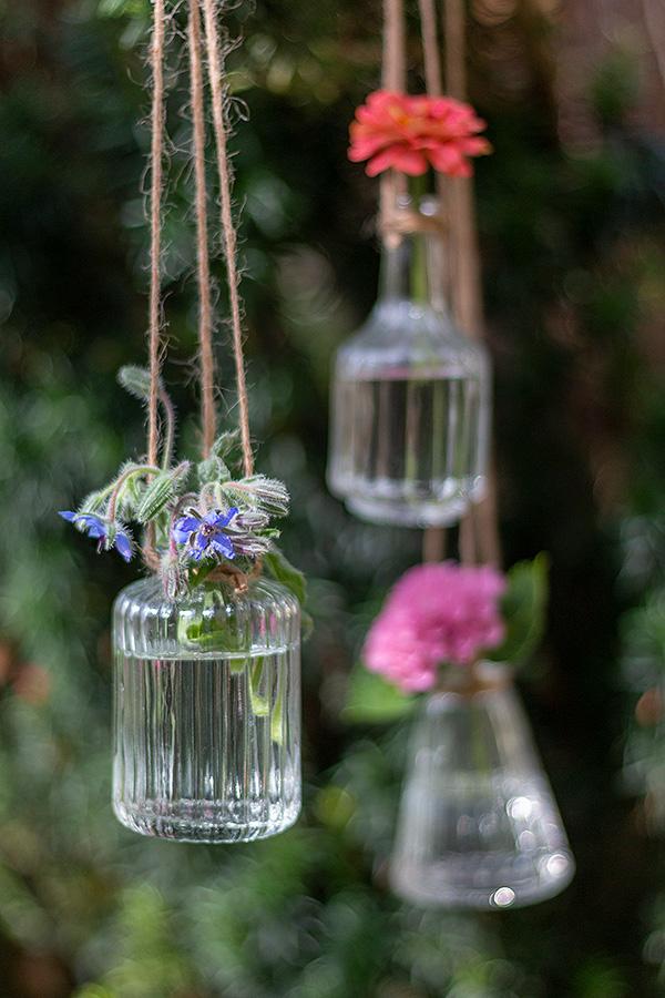 Hängevasen für die Gartenparty mit Blumen bestückt