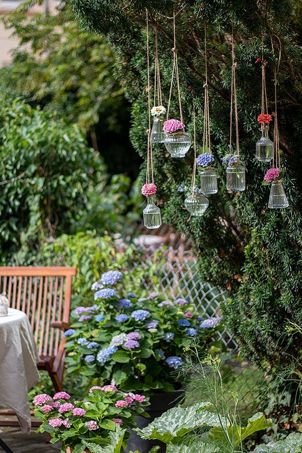 Hängevasen mit Blumen bestückt für die Gartenparty