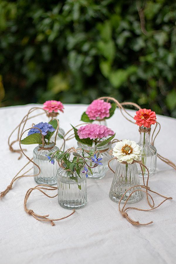Vasen mit Wasser auffüllen und mit Blumen bestücken