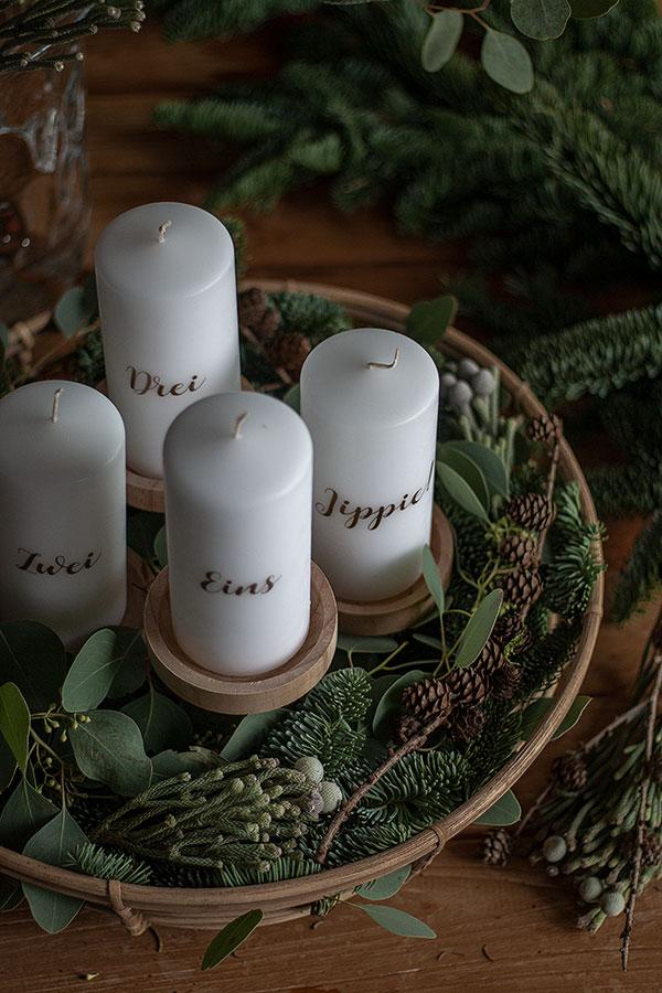 4. Schritt: Kerzen auf die Kerzenständer stellen und mit Lärchenzweigen und kleinen Tannenzweigen dekorieren