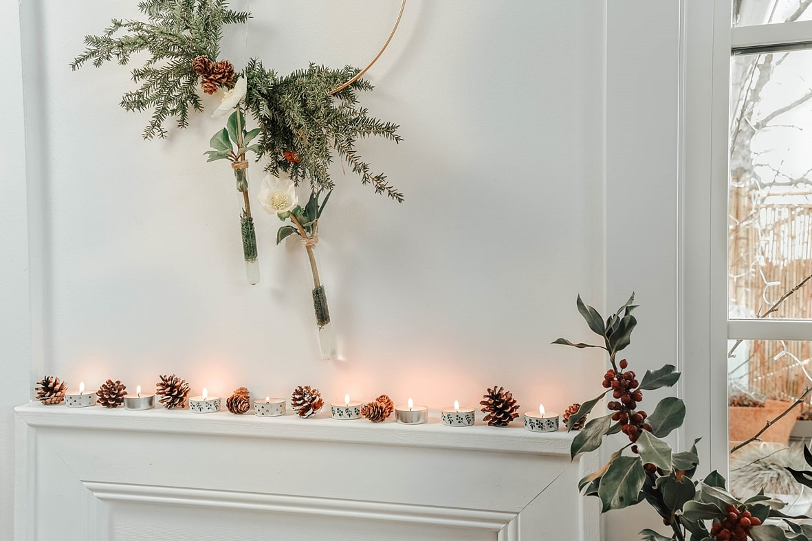 Winterdeko mit Kerzen und Zapfen