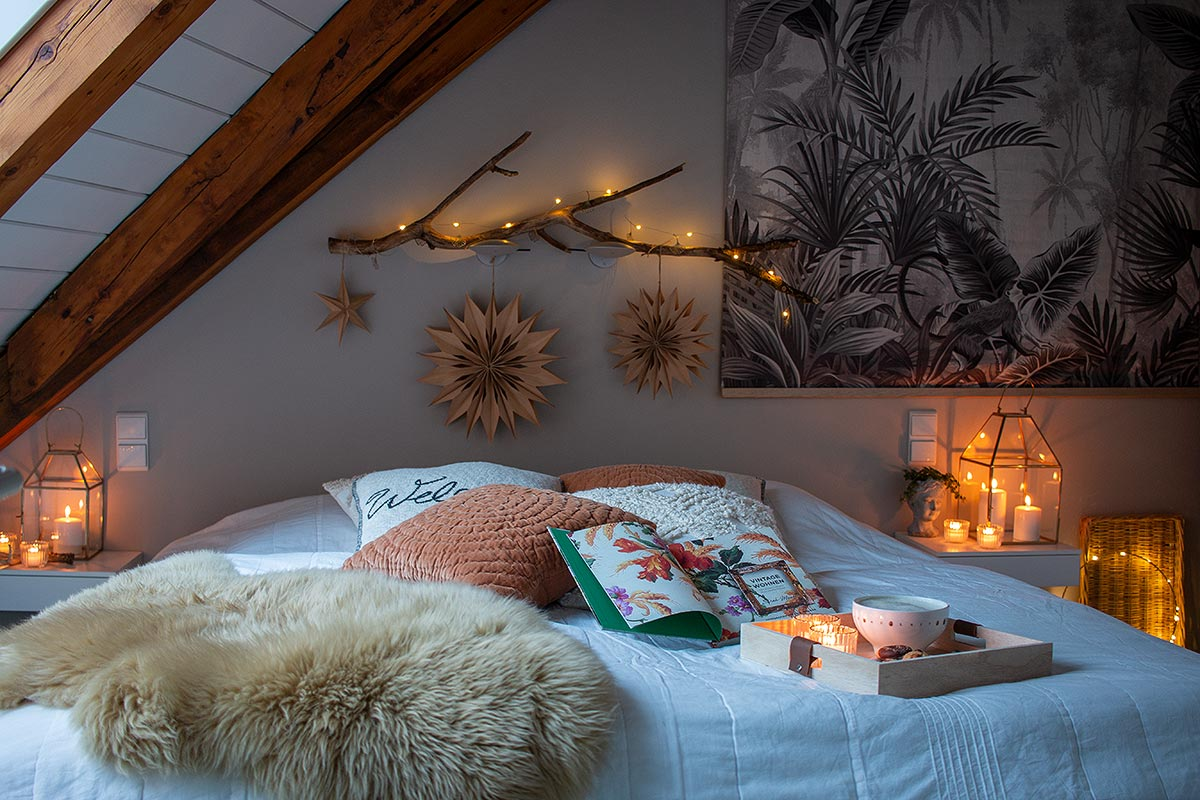 Felle, Kissen, Kerzen, Lichterketten sorgen für Gemütlichkeit im Schlafzimmer