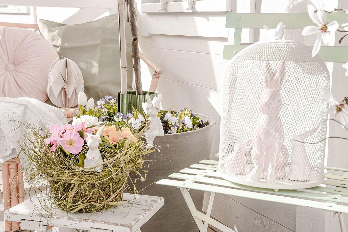 Osterdeko mit Porzellanhasen und Blumen.