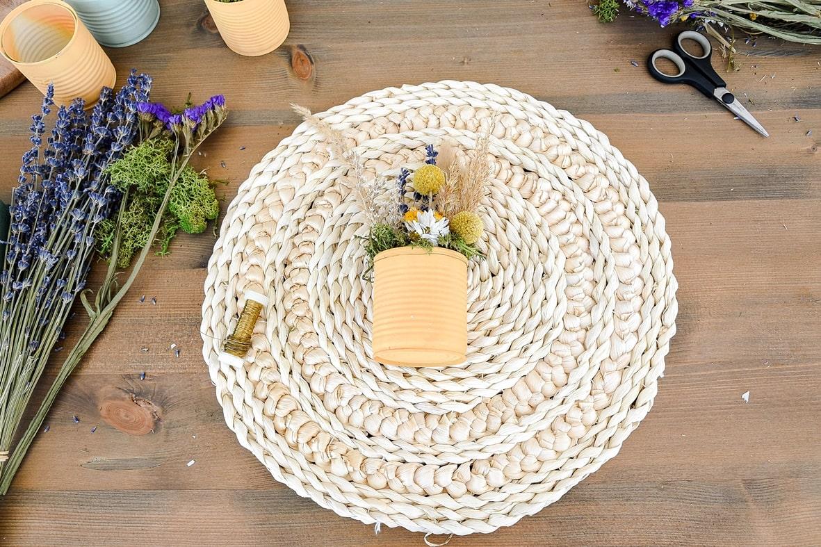 Dosen mit Basteldraht auf Tischsets befestigen.
